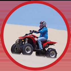 Person riding ATV on dunes