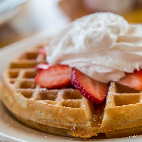 Waffle topped with fresh strawberries and whipped cream