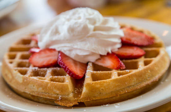 waffles topped with fresh strawberries and whipped cream